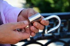 La mano apre una serratura chiave Fotografia Stock Libera da Diritti
