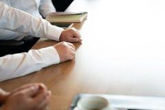 La mano ascendente cercana de los hombres de negocios, est?n hablando juntos en la tabla de madera en la tarde fotografía de archivo