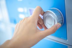 La mano ascendente cercana está dando vuelta al botón del dial de la lavadora del lavadero imágenes de archivo libres de regalías