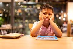 La mano asiatica del ragazzo di scuola sul suo fronte si è vestita mentre faceva il suo lavoro domestico fotografie stock