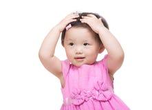 La mano asiatica della bambina due tocca i suoi capelli Fotografia Stock