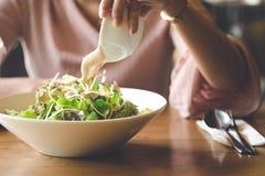 La mano asiatica della donna sta versando condire ed il cibo dell'insalata di verdure immagine stock libera da diritti