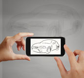 La mano astuta facendo uso del telefono di touch screen prende la foto dell'icona dell'automobile Fotografia Stock