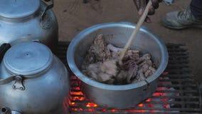 La mano aumenta la tapa de Pan And Stir The Chicken con una cuchara almacen de metraje de vídeo