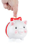 La mano baja una moneda en un rectángulo de la uno-moneda del cerdo Imagen de archivo libre de regalías