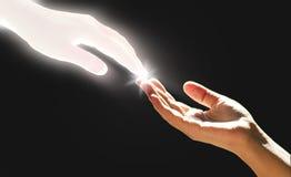 La mano blanca del ` s de dios está tocando la mano