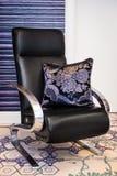 La mano bordó la almohada violeta y negra en la silla negra Foto de archivo
