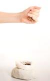 La mano cae monedas al bolso Fotografía de archivo
