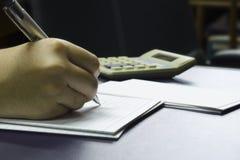 La mano calcula número con el fondo de la calculadora Foto de archivo libre de regalías