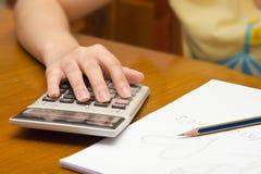 La mano calcula número con el fondo de la calculadora Fotografía de archivo