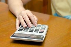 La mano calcula número con el fondo de la calculadora Fotografía de archivo libre de regalías