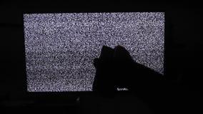 La mano cambia los canales ningún fondo del ruido TV del hombre Pantalla de la televisión con el ruido estático causado por la ma almacen de metraje de vídeo