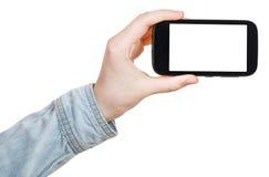 La mano in camicia giudica lo smartphone isolato Immagini Stock