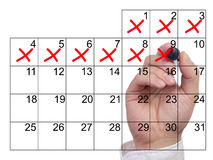 La mano cancella i giorni nel rosso da un calendario Fotografia Stock
