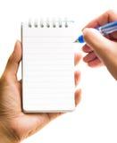 La mano cattura una nota sul blocchetto per appunti in bianco Fotografia Stock
