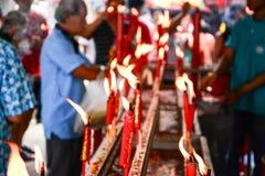 La mano cense el palillo de ídolo chino a la vela ardiente Imagen de archivo libre de regalías