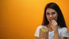 La mano che dà le patate fritte alla ragazza, la società si abitua la generazione ad alimenti industriali archivi video