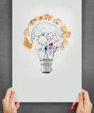 La mano che disegna la lampadina con la matita ha visto la polvere ed innesta l'icona Immagini Stock Libere da Diritti