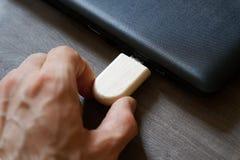 La mano che inserisce la chiavetta USB si collega al computer portatile alimentabile del computer della porta USB per i dati di t Fotografie Stock