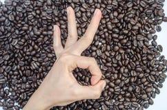 La mano che produce approvazione del segno ed i chicchi di caffè Fotografie Stock