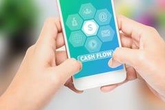 La mano che tiene il messaggio del FLUSSO DI CASSA dell'etichetta del telefono, può essere utilizzata nella pubblicità immagine stock