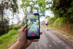 La mano che tiene un cellulare che gioca Pokemon va Fotografia Stock