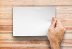 La mano che tiene una carta di note su fondo di legno Immagini Stock Libere da Diritti