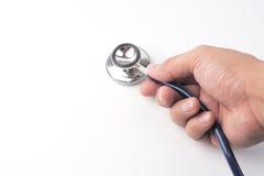 La mano che tiene uno stetoscopio, fondo bianco fotografie stock