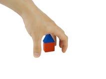 La mano colgó sobre la casa en un fondo blanco Foto de archivo libre de regalías