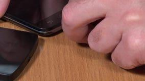 La mano collega il cavo bianco e nero del usb del micro agli Smart Phone stock footage