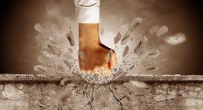La mano colpisce intenso e le rotture mettono il bastone tra le ruote immagine stock