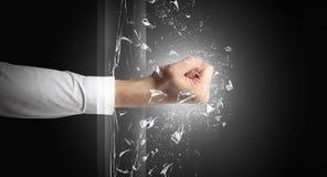 La mano colpisce intenso e rompe i vetri fotografie stock