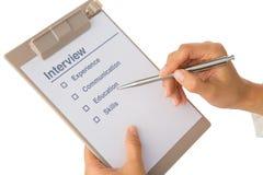La mano compila la lista di controllo di intervista di lavoro Fotografie Stock