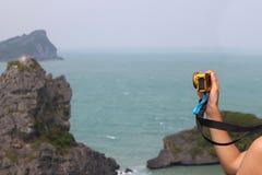 La mano con la cámara de GoPro encima de la montaña, las islas y el océano compiten Imagen de archivo libre de regalías