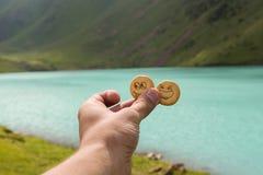 La mano con 2 cracker divertenti si avvicina al lago Immagini Stock