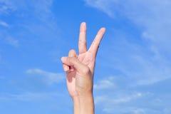 La mano con due dita aumenta la vittoria Immagini Stock