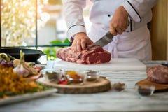 La mano con el cuchillo corta la carne Foto de archivo