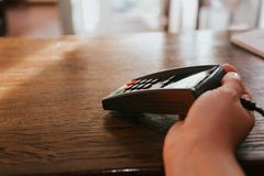 La mano con el terminal y la tarjeta del crédito del cliente Pago por la tarjeta fotografía de archivo libre de regalías