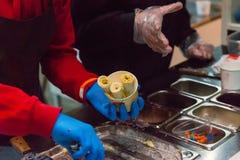 La mano con guantes dobla en helado tailandés delicioso cocinado taza Fotografía de archivo libre de regalías