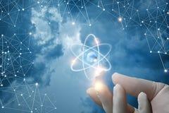 La mano con guantes muestra el átomo Fotos de archivo libres de regalías