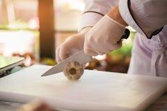 La mano con il coltello taglia l'aglio immagini stock