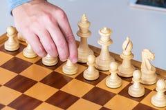 La mano con il pegno fa il primo movimento sulla scacchiera Immagini Stock