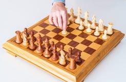 La mano con il pegno fa il primo movimento sulla scacchiera Fotografia Stock