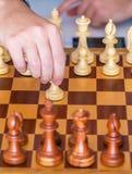 La mano con il pegno fa il primo movimento sulla scacchiera Fotografie Stock Libere da Diritti