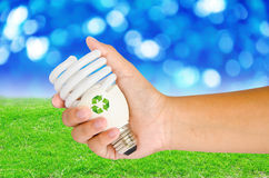 La mano con la lampada ed il segno riciclano Fotografia Stock