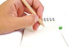 La mano con la matita prende le note in un taccuino su bianco Fotografie Stock Libere da Diritti