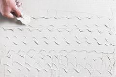 La mano con la spatola fa il modello su gesso bianco Fotografia Stock