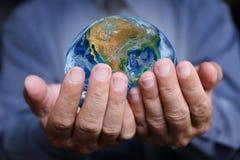 La mano con la tierra, elementos del hombre de negocios de esta imagen se suministra Foto de archivo libre de regalías