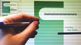 La mano con la penna indica lo schermo con la proiezione di diapositive di programma della presentazione di scorrevoli fotografia stock libera da diritti