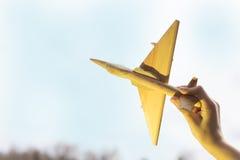 La mano con un aeroplano de madera en el fondo de la puesta del sol Aero- Alca L-159 Imágenes de archivo libres de regalías